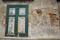 Una ventana verde vieja en la pared agrietada imágenes de archivo libres de regalías