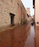 Una via bagnata del mattone in Certaldo Italia fotografia stock