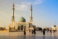 Una via della città con la gente che cammina accanto alla moschea persiana iraniana magnifica Fatima Masumeh Shrine in blu immagine stock libera da diritti