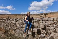 Una viandante che attraversa una scaletta sulla pietra fotografie stock