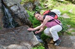 Una viandante vicino al brooklet della montagna Fotografia Stock Libera da Diritti