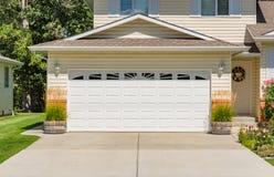 Una vicinanza perfetta Casa della famiglia con l'ampia porta del garage e strada privata concreta nella parte anteriore fotografia stock libera da diritti