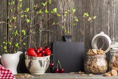 Una vida casera simple de la cocina aún con los ingredientes para un desayuno sano, el cereal forma escamas, las fresas en una os Foto de archivo