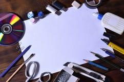 Una vida de la escuela o todavía de la oficina con una hoja de papel en blanco blanca y muchos materiales de oficina Las fuentes  Fotografía de archivo