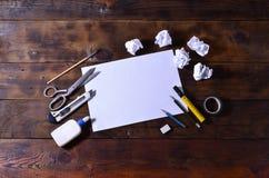 Una vida de la escuela o todavía de la oficina con una hoja de papel en blanco blanca y muchos materiales de oficina Las fuentes  fotos de archivo libres de regalías