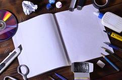 Una vida de la escuela o todavía de la oficina con un cuaderno de la escuela o un talonario de cheques abierto y muchos materiale fotografía de archivo