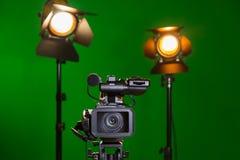 Una videocamera e un riflettore con una lente di Fresnel su un fondo verde Contaminazione nell'interno La chiave di intensità fotografia stock