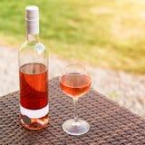 Una vidrio y botella de vino rosado rojo o en viñedo del otoño en la tabla de mimbre de madera Tiempo de cosecha, comida campestr Fotos de archivo