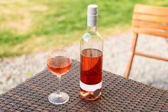 Una vidrio y botella de vino rosado rojo o en viñedo del otoño en la tabla de mimbre de madera Tiempo de cosecha, comida campestr Foto de archivo