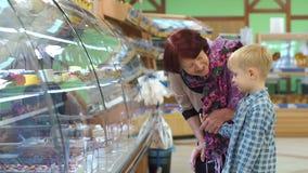 Una vieja abuela con un pequeño nieto en el supermercado elige los dulces almacen de metraje de vídeo