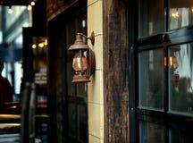 Una vieja ejecución de la linterna delante de una casa tradicional Imagen de archivo libre de regalías