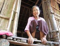 Una vieja mujer de Chin con un tatuaje facial que se sienta en la entrada de su casa de bambú imagen de archivo