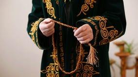 Una vieja mulá en vestido nacional que ruega con el rosario gotea en manos