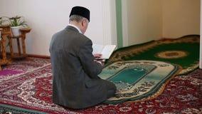 Una vieja mulá que ruega con el Corán en sus manos