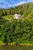 Una villa a tre livelli accogliente è posizionata sul pendio di alta montagna verde vicino ad un bello lago Immagine Stock