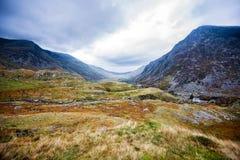 Una visión abajo del valle de Nant Ffrancon hacia la isla de Anglesey y del mar Fotografía de archivo