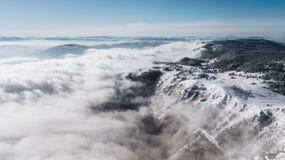 Una visión desde arriba de la montaña a los acantilados cubiertos con nieve y al valle del pino con un cielo azul claro en un día fotos de archivo libres de regalías