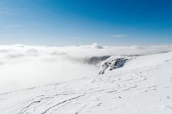 Una visión desde arriba de una montaña nevosa a un valle cubierto por una niebla en un día soleado con un cielo azul claro foto de archivo