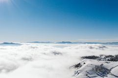 Una visión desde arriba de una montaña nevosa a un valle cubierto por una niebla en un día soleado con un cielo azul claro imagenes de archivo