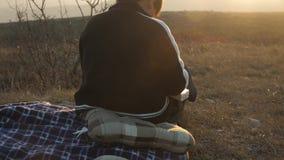 Una visión desde detrás de un muchacho que lee un libro en los rayos de la puesta del sol en naturaleza almacen de metraje de vídeo