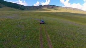 Una visión desde el aire para poner verde prados, colinas en la distancia y montar del coche campo a través en la república de Kh metrajes