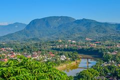 Una visión desde la colina de Phou Si, Laos a través del puente a los tejados y a las colinas coloridos más allá foto de archivo libre de regalías