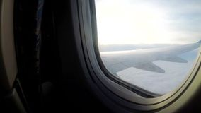 Una visión desde la ventana de un aeroplano del pasajero que vuela bajo sobre las nubes en mún tiempo almacen de metraje de vídeo