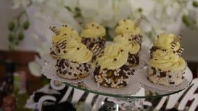 Una visión desde lejos en un pastel de bodas imponente que se coloca en los dulces golpea almacen de metraje de vídeo