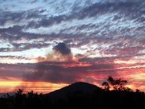 Una visión distante en la puesta del sol de los granjeros que queman la caña de azúcar antes del machacamiento Imagen de archivo