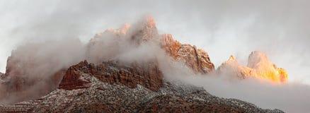 Una visión panorámica muestra el Mt Kinesava con nieve en ella y nubes que la rodean en la primera luz en una mañana de diciembre fotos de archivo libres de regalías