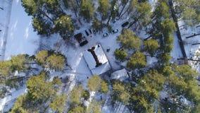 Una vista aérea de una casa cubierta en nieve en el bosque almacen de metraje de vídeo