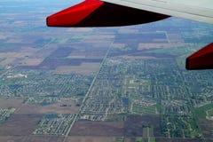 Una vista aerea di paesaggio suburbano vista attraverso una finestra dell'aeroplano Fotografia Stock Libera da Diritti