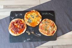 Una vista aerea di tre pizze su un contorno nero del bordo con farina ed il fiore asciutto immagine stock