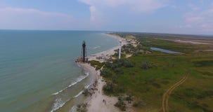 Una vista aerea stupefacente di un segnale bianco e di una torre nera del confine sull'isola di Dzharylhach con il litorale merav video d archivio