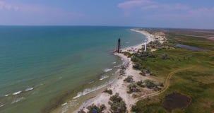 Una vista aerea stupefacente di un segnale bianco e di una torre nera del confine sull'isola di Dzharylhach con il litorale merav archivi video
