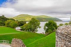 Una vista al lago loch Ness y a las montañas escocesas del castillo de Urquhart imagenes de archivo