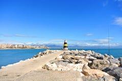 Una vista al mar Mediterráneo, a un faro con los rompeolas, a las cañas de pescar de locals y a Torremolinos en el fondo Fotografía de archivo libre de regalías