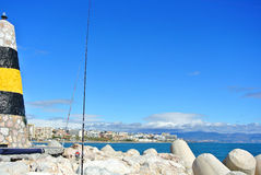 Una vista al mar Mediterráneo, a un faro con los rompeolas, a las cañas de pescar de locals y a Torremolinos en el fondo Fotos de archivo libres de regalías