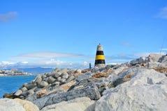 Una vista al mar Mediterráneo, a un faro con los rompeolas, a las cañas de pescar de locals y a Torremolinos en el fondo de un em Imagenes de archivo