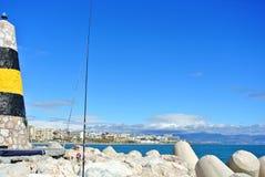 Una vista al mar Mediterraneo, ad un faro con i frangiflutti, alle canne da pesca dei locali ed a Torremolinos ai precedenti Fotografie Stock Libere da Diritti