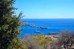 Una vista attraverso gli alberi del livello del mare blu azzurrato nella baia nel mar Mediterraneo Immagine Stock