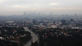 Una vista crepuscular del centro de ciudad de Los Ángeles con una autopista ocupada en el primero plano metrajes