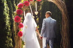 Una vista da dietro su una coppia di nozze che cammina da un altare Immagine Stock