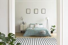 Una vista da una stanza differente in un interno pastello della camera da letto con un grande letto nel mezzo e una lampada e un  immagini stock