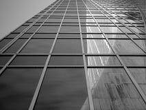 Una vista dal marciapiede davanti ad una ruspa spianatrice di vetro del cielo mostra una riflessione della costruzione della toll fotografia stock libera da diritti
