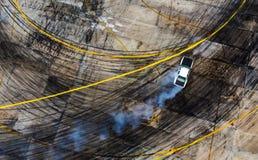 Una vista dall'aria che corre l'automobile della deriva con molto fumo sul fotografia stock