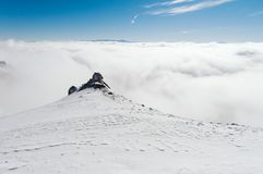 Una vista dalla cima di una montagna nevosa ad una valle coperta da una nebbia un giorno soleggiato di chiaro cielo blu fotografia stock