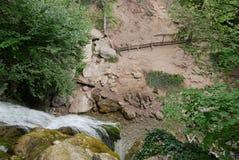 Una vista de arriba hacia abajo de una cascada que fluye sobre rocas Formación debajo de una pequeña charca y funcionamiento más  Fotos de archivo libres de regalías
