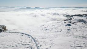 Una vista de la cuesta nevosa en el valle cubierto con niebla imagenes de archivo