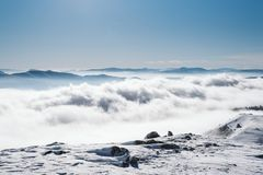 Una vista de la cuesta nevosa en el valle cubierto con niebla fotografía de archivo libre de regalías